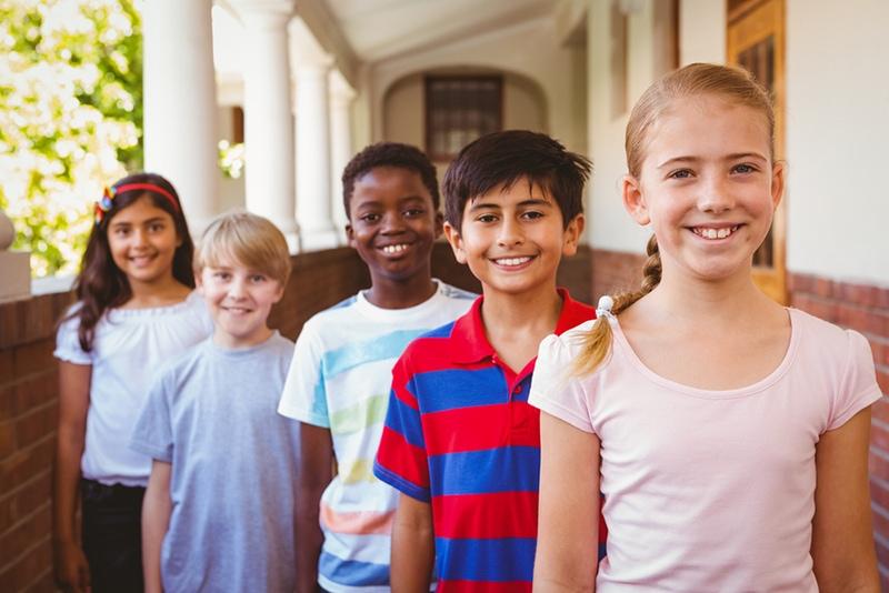 lächelnde Schulkinder, die in einer Reihe auf dem Schulhof stehen