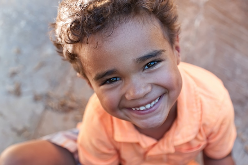 lächelnder Junge im orangefarbenen Hemd, der auf dem Boden sitzt