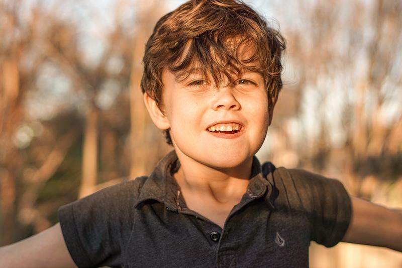 lächelnder kleiner Junge, der draußen in der Sonne steht