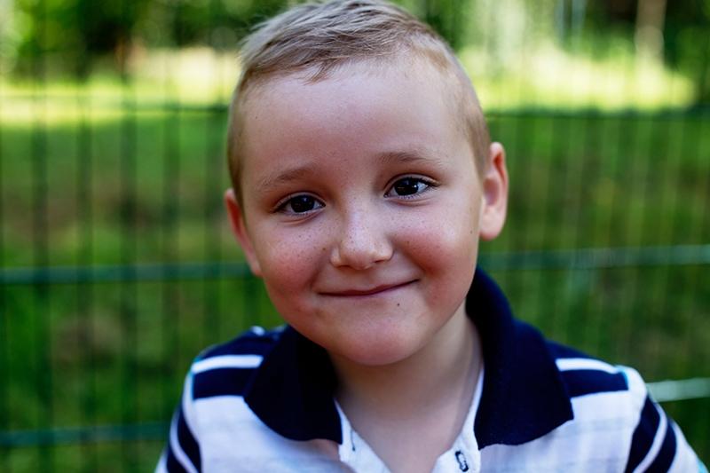 lächelnder kleiner Junge im Poloshirt, der in der Nähe des Zauns steht