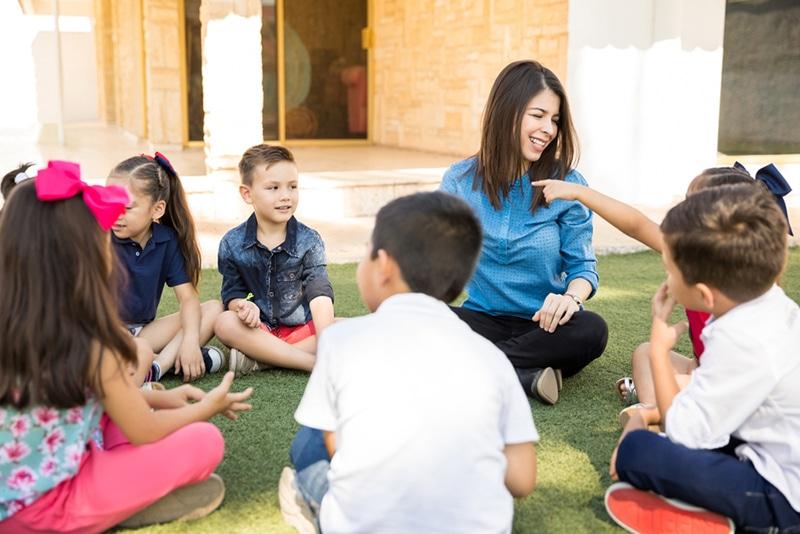 lächelnder Lehrer, der mit Kindern im Kreis im Freien sitzt und ein Spiel spielt