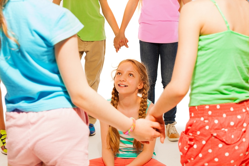 smiling girl sitting on the ground while their friends standing in a circle around her
