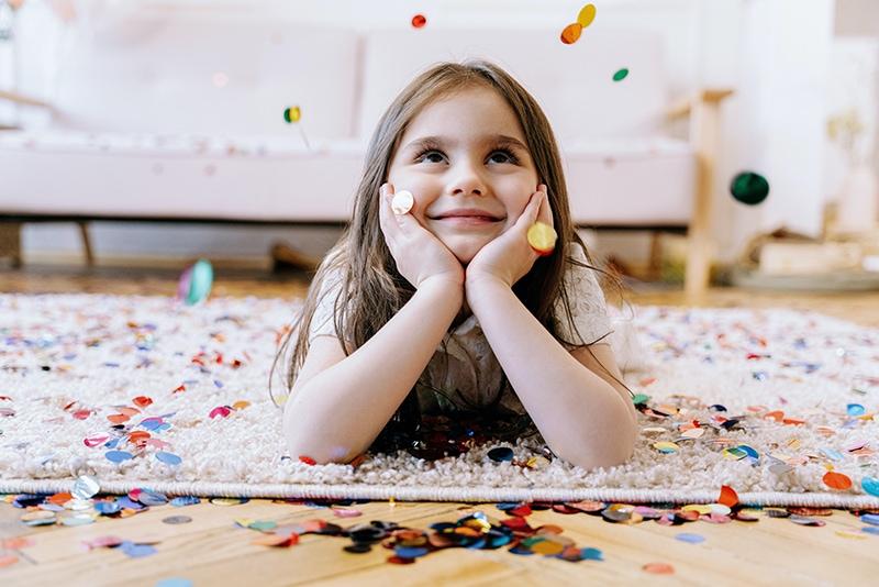 lächelndes Mädchen, das auf dem Teppich liegt, während Konfetti auf sie fällt