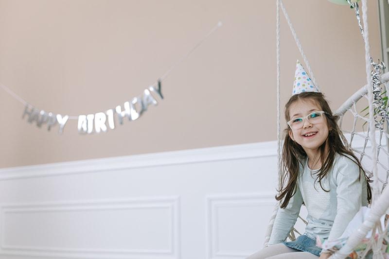lächelndes Mädchen, das auf einer Geburtstagsfeier auf einer Schaukel sitzt