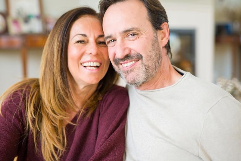 lächelndes Paar mittleren Alters, das zu Hause sitzt