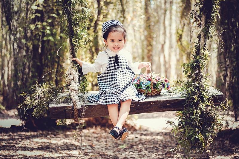 lächelndes kleines Mädchen, das auf der Schaukel sitzt und einen Korb mit Blumen hält
