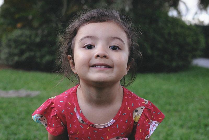 lächelndes kleines Mädchen im roten Kleid, das im Park steht