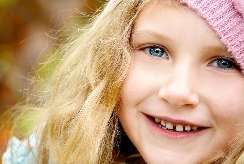 lächelndes kleines Mädchen mit blauen Augen und blonden Haaren