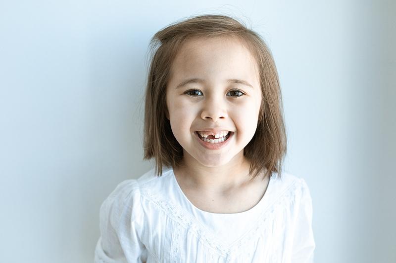 lächelndes kleines Mädchen mit kurzen Haaren in weißer Bluse