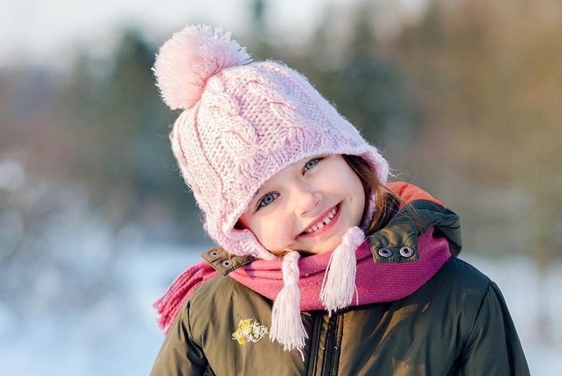 lächelndes kleines Mädchen mit rosa Strickmütze und grüner Jacke