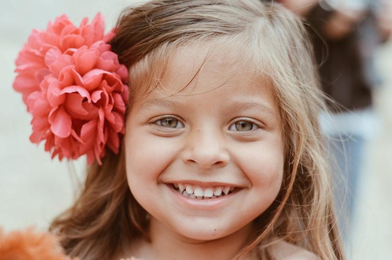 lächelndes kleines Mädchen mit rosa Blume im Haar