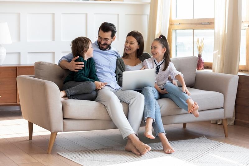 lachende Familie, die auf der Couch sitzt und Laptop benutzt