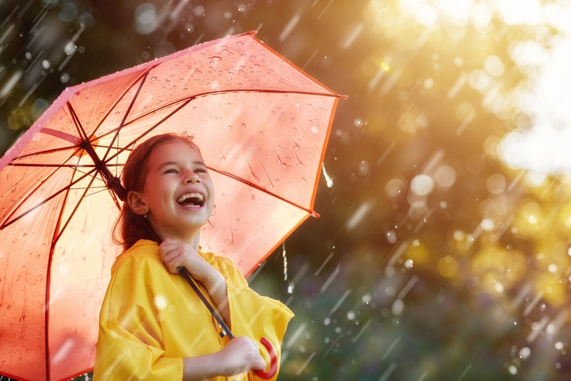 lustiges Kind mit rotem Regenschirm