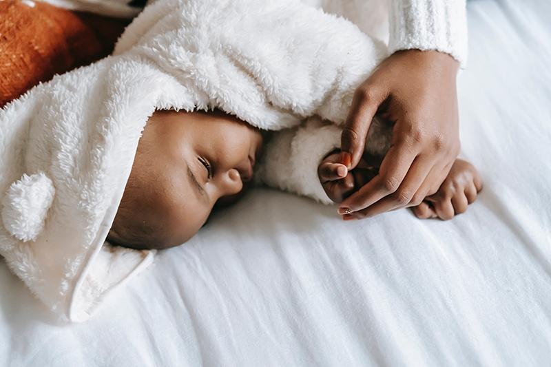 Mutter hält Hand ihres Babys, das im Bett schläft