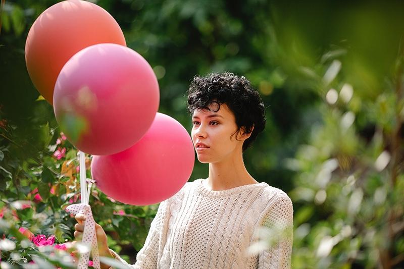 nachdenkliche Frau, die Luftballons hält, während sie im Garten steht