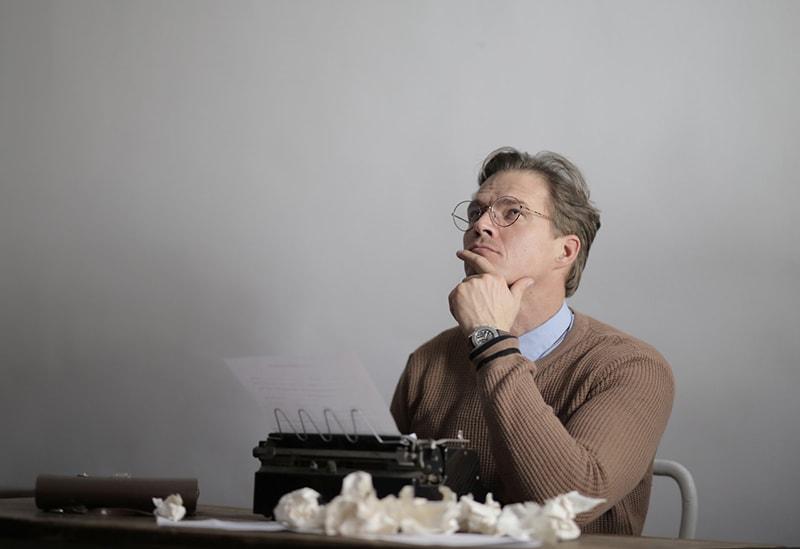 nachdenklicher Mann, der aufschaut, während er vor der Schreibmaschine sitzt