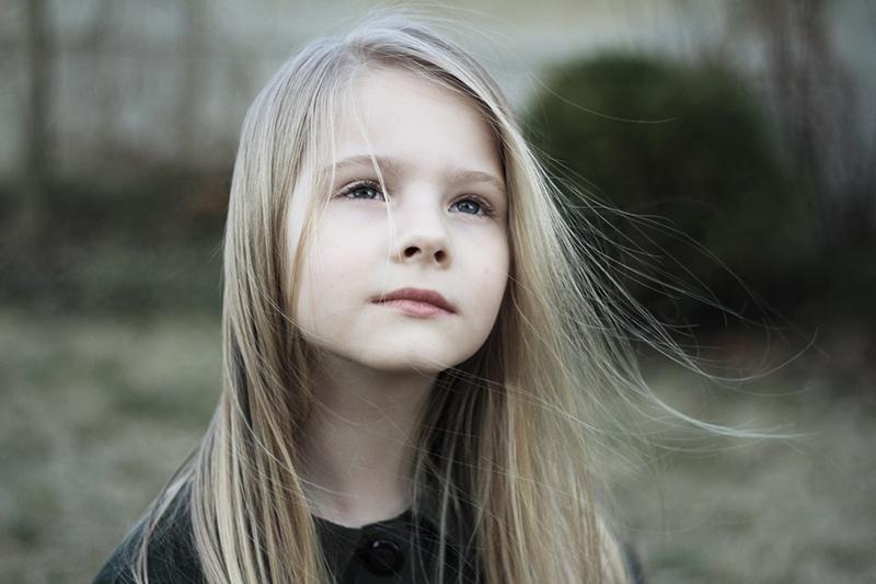 nachdenkliches junges Mädchen mit blonden Haaren, das gerade nach oben schaut