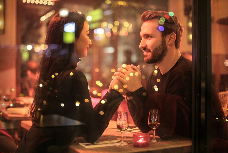 romantisches Paar Händchen haltend im Restaurant