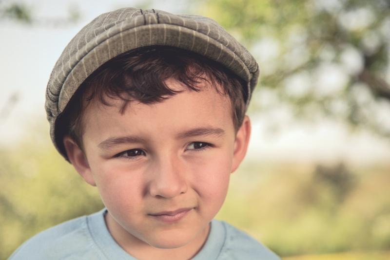 süßer kleiner Junge mit Hut draußen