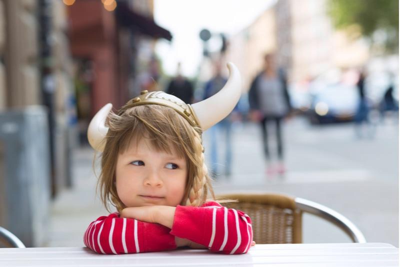 süßes kleines Mädchen, das im Café sitzt