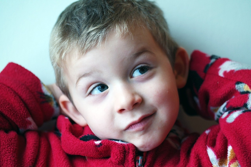 süßer Junge im roten Pullover, der beiseite schaut
