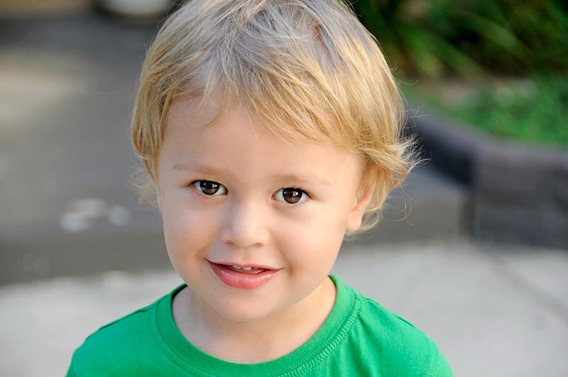 süßer blonder kleiner Junge im grünen T-Shirt