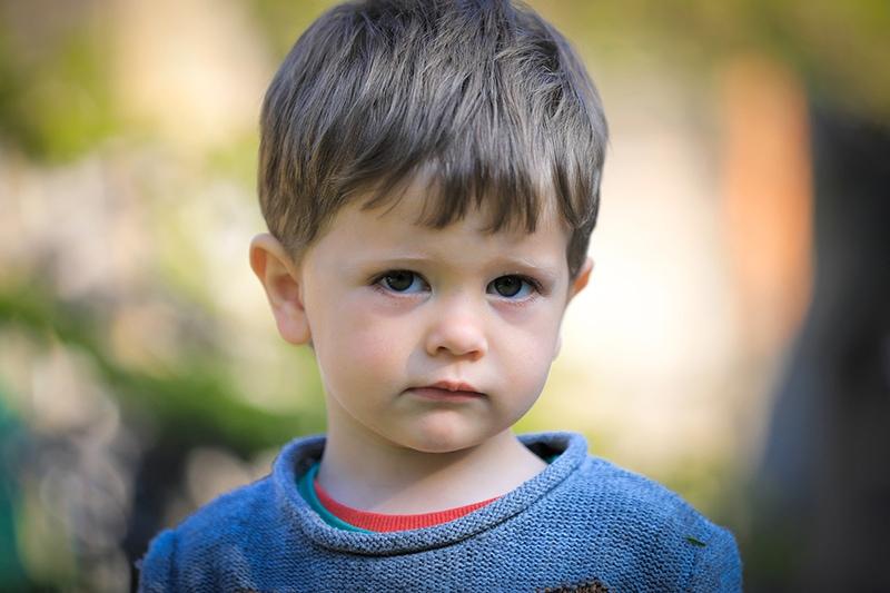 süßer kleiner Junge im blauen Pullover, der im Freien steht