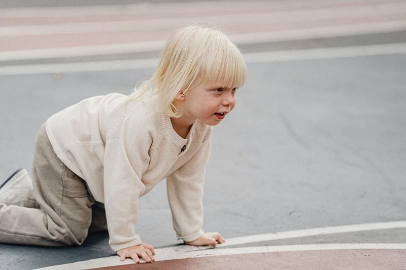 süßer kleiner Junge krabbelt auf dem Spielplatz