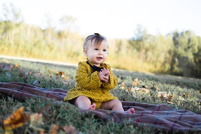 süßes Baby im gelben Kleid sitzt auf der Decke im Park