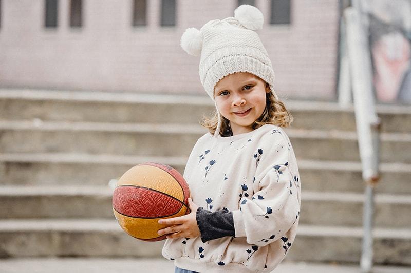 süßes Mädchen, das einen Ball auf der Straße hält