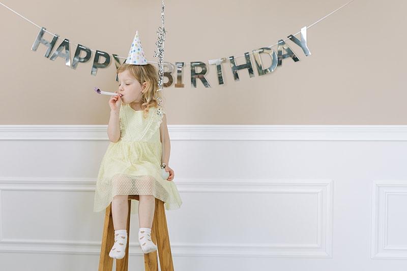 süßes kleines Mädchen bläst in ein Partyhorn, während es auf dem Stuhl sitzt