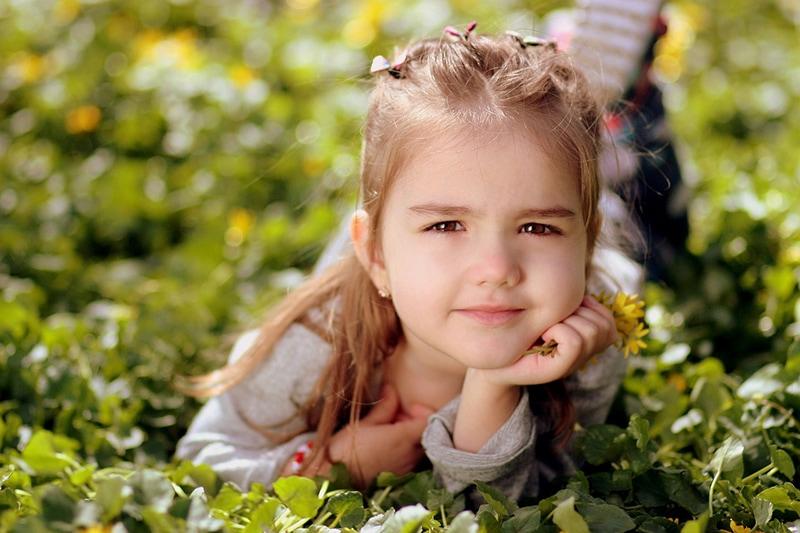 süßes kleines Mädchen, das auf dem Gras liegt und Blumen hält