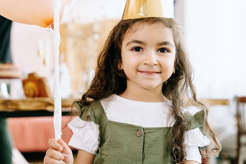 süßes kleines Mädchen, das den Ballon auf der Geburtstagsfeier hält