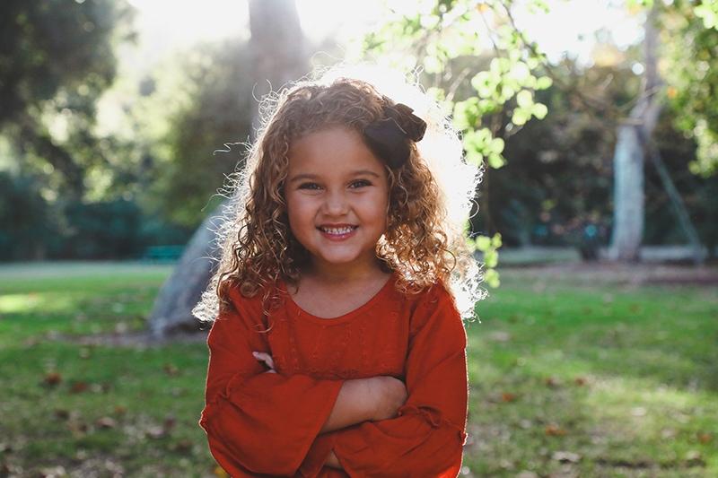 süßes kleines Mädchen im roten Kleid, das im Park steht