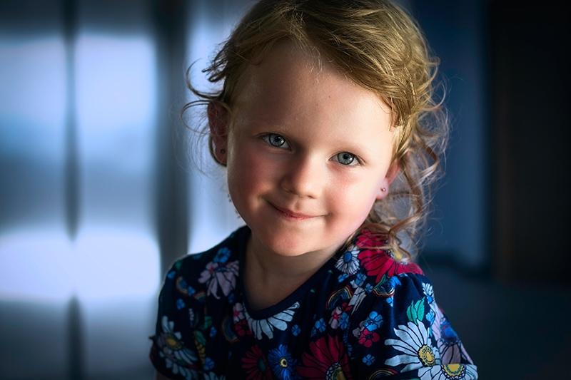 süßes kleines Mädchen mit blonden Haaren im Blumenhemd