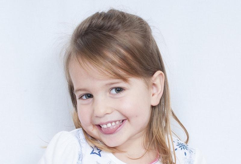 süßes lächelndes kleines Mädchen, das ihre Zunge zeigt