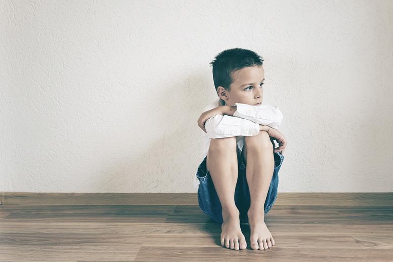 trauriger Junge denkt auf dem Boden sitzend