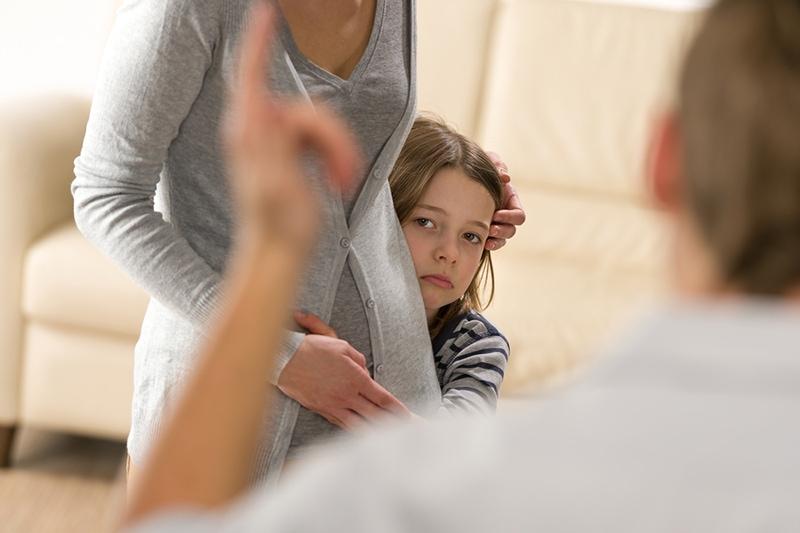 verängstigtes kleines Mädchen, das sich hinter ihrer Mutter vor dem verärgerten Vater versteckt