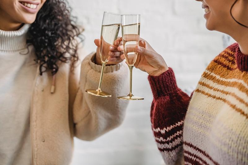 zwei Freundinnen, die mit Champagner anstoßen und Geburtstag feiern