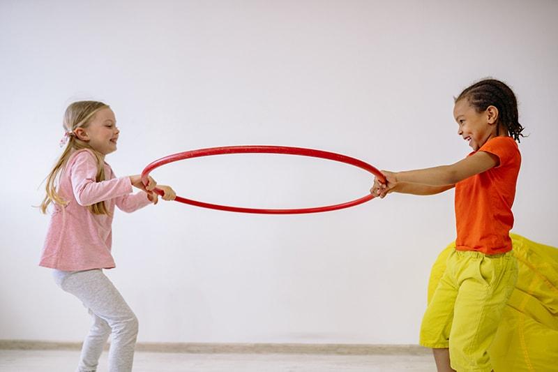 zwei Kinder, die einen Hula-Hoop-Reifen im Zimmer halten
