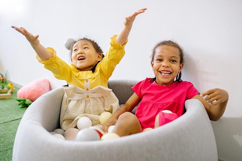 Zwei glückliche Mädchen, die Spaß beim Spielen mit Plastikbällen haben