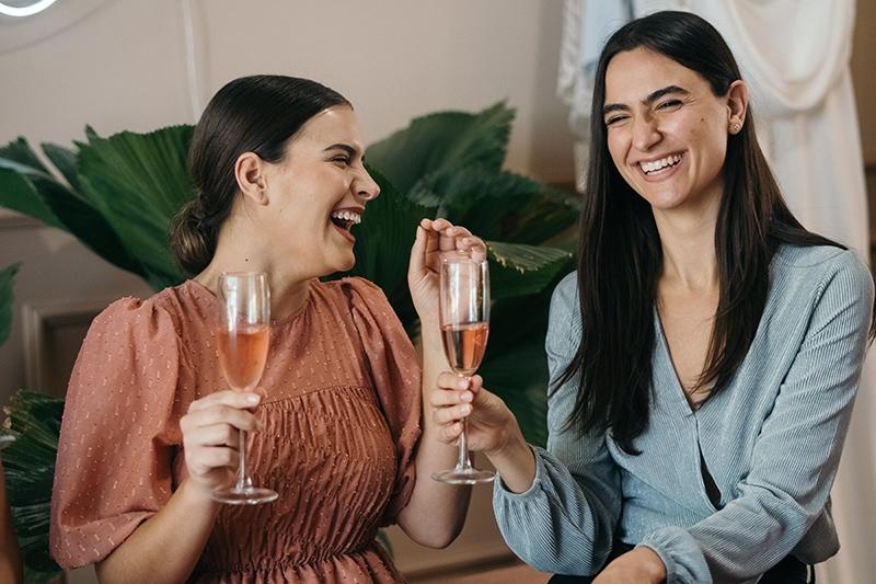 zwei lächelnde Freundinnen, die Champagner trinken