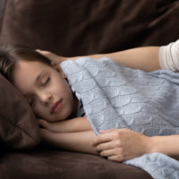 Mama bedeckt verschlafenes Kind mit Decke