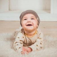 Baby liegt auf Teppich