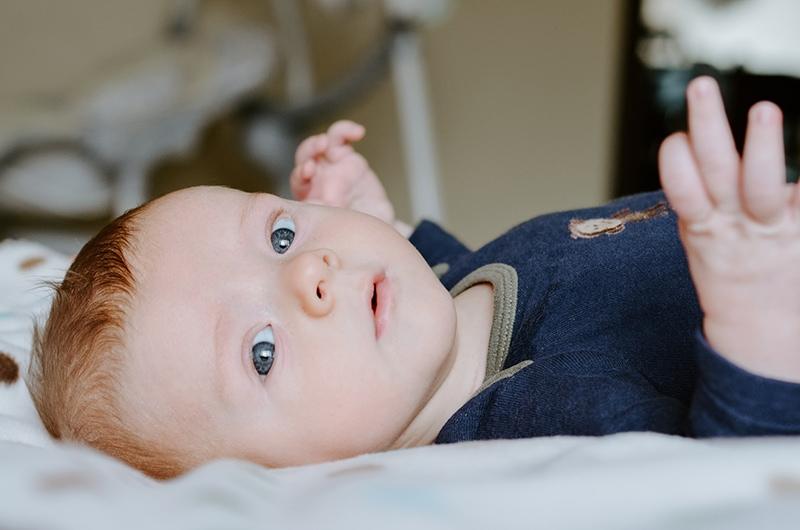 Baby Junge im blauen Body liegt auf dem Bett