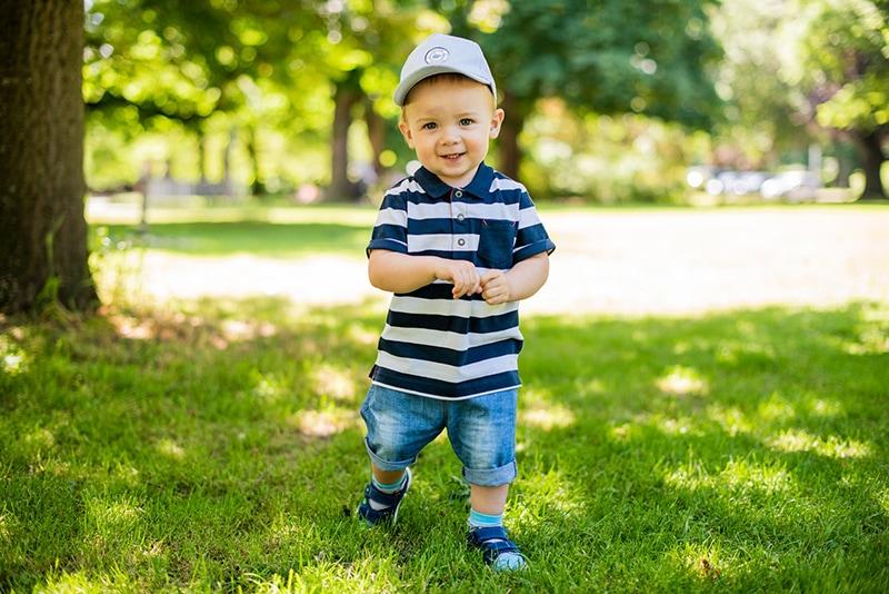 Baby mit Mütze steht auf dem Gras