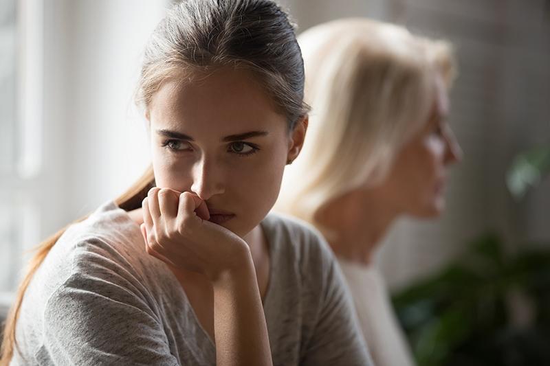 Beleidigte erwachsene Tochter und ältere Mutter, die zu Hause sitzen