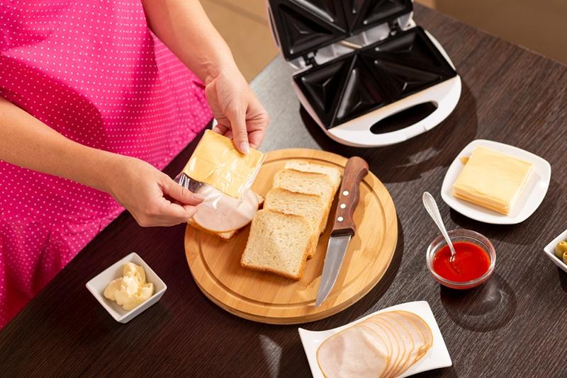 Frau fügt eine Käsescheibe auf ein Sandwich und macht heiße Sandwiches