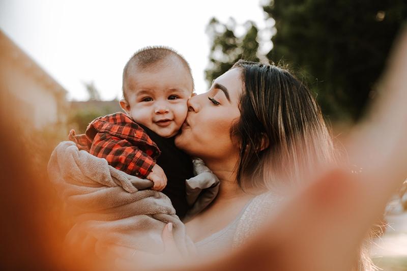 Frau küsst ihr Baby, während sie es hält