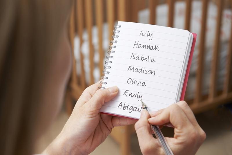 Frau schreibt mögliche Namen für kleines Mädchen im Kinderzimmer